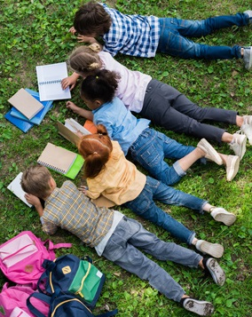 Kids reading in the grass.