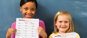 Two young girls smiling and holding up their homework with an A grade on it